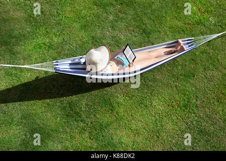 High Angle View Of Young Woman Reading Ebook On Hammock - Stock Photo