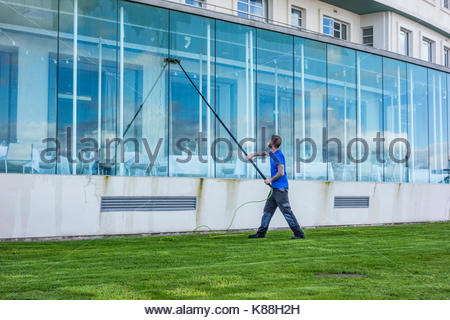 Cleaning the front windows of the Midland Hotel on Morecambe Promenade - Stock Photo