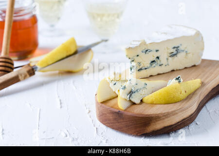 Blue cheese  served with fresh pear and honey on rustic cutting board, cheese platter - Stock Photo
