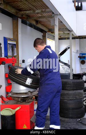Mechanic changing a flat tyre - Stock Photo