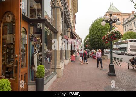 Victoria, British Columbia, Canada - 6 September 2017: Pedestrians walking on sidewalk on Government Street - Stock Photo