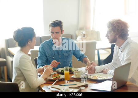 Productive negotiations at modern restaurant: young business partners discussing details of mutually beneficial - Stock Photo