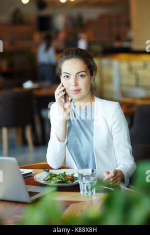 Waist-up portrait of confident young entrepreneur looking at camera with small smile while conducting telephone - Stock Photo