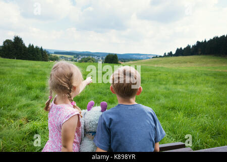 Cute child couple sitting on bench with view on mountains - Stock Photo
