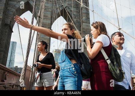 Tourists on the Brooklyn Bridge, New York, New York. - Stock Photo