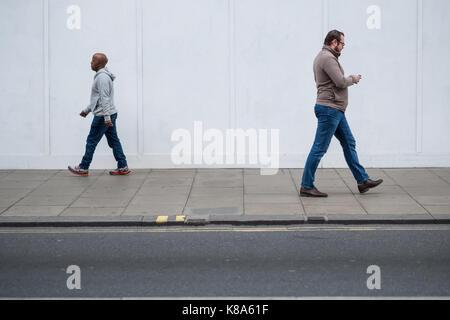 Two men walk in opposite directions on London's Oxford Street, UK - Stock Photo