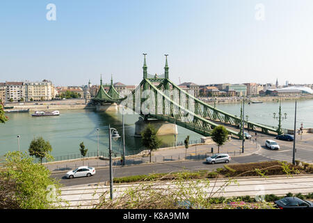 The Liberty Bridge in Budapest, Hungary with some old trams in the foreground passing by. - Stock Photo