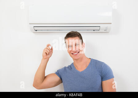 Portrait Of Happy Man Using Remote Control To Operate Air Conditioner - Stock Photo