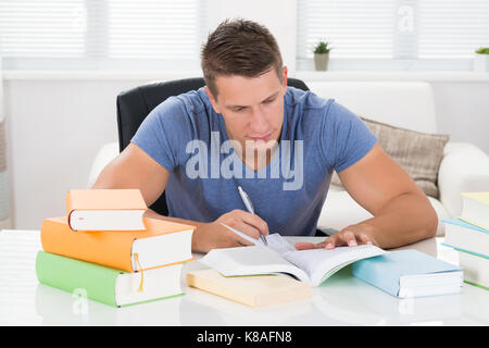 Young Man Reading Books At Desk In Living Room - Stock Photo