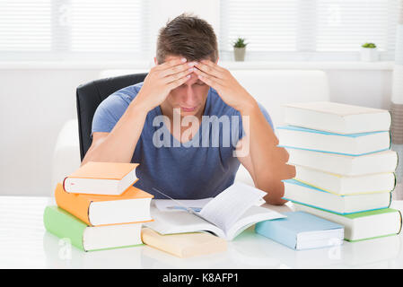 Portrait Of Tired Young Man Studying Books At Desk - Stock Photo