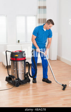 Happy Male Janitor Vacuuming Wooden Floor In House Stock Photo