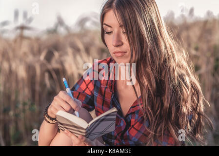 Beautiful brunette girl field, shirt. Concept new ideas, writing in notebook. A woman writes in a notebook. The - Stock Photo