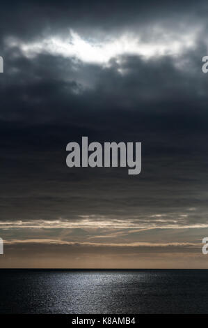 Seascape as night approaches, with grey clouds in a dark moody sky and light rays softly scattering light on water. - Stock Photo