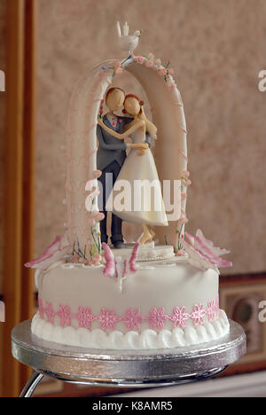 the top tier of a wedding cake with a model of a bride and groom standing on the cake under an archway. pink and - Stock Photo