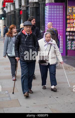 Elderly Asian couple, one using an oxygen tank, walking along a street - Stock Photo