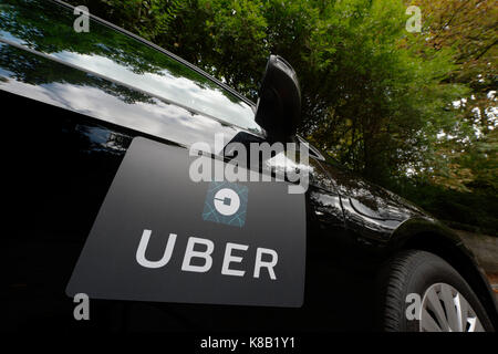 A black Volkswagen featuring the Uber logo is used as a taxi and also shows a driver in a leafy suburban street - Stock Photo