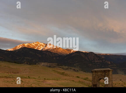 Electric Peak at Sunset with the foothills, valley and Roosevelt Arch in the foreground. - Stock Photo