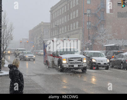 Ambulance in traffic during snowstorm - Stock Photo