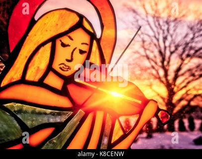 An angel playing the violin. Stained glass angel. Winter background. Colorful scenery. Sun shining through the stained - Stock Photo