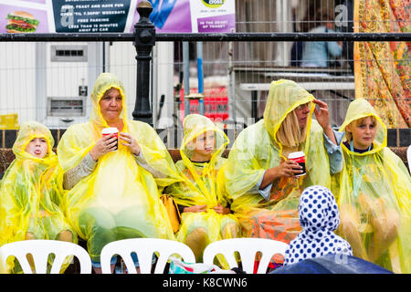 England, Broadstairs. Two adults, women, holding coffee cups, and three children all sitting outside in yellow ponchos - Stock Photo