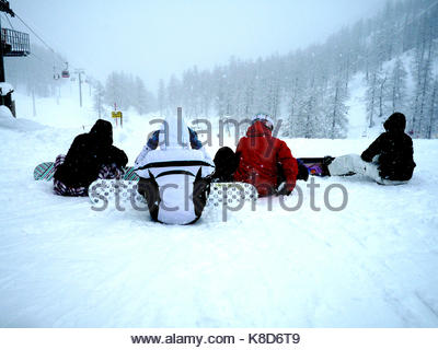4 snowboarders sitting on the snow - Stock Photo