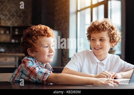Adorable curly haired brothers spending time together - Stock Photo