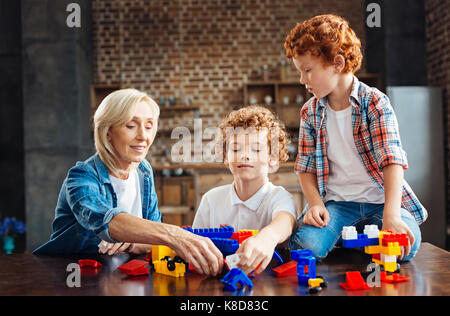 Loving grandmother playing with kids at home - Stock Photo