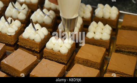 Cream being squeezed onto chocolate cakes. Squeezing the cream on the cake - Stock Photo