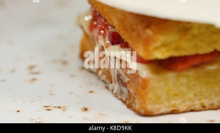 Sponge cake with strawberries, jam and whipped cream with a cut out piece - Stock Photo