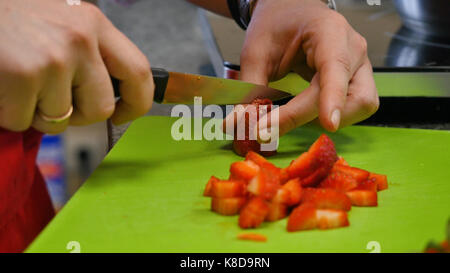 Chef Hand and Knife Slicing Fresh strawberry on cutting board
