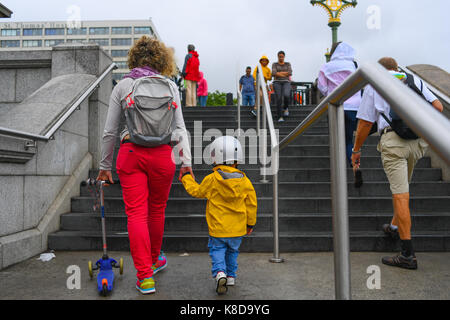 Brightly clothed Mother and son walks hand in hand  in London England carrying aand riding a scooter - Stock Photo