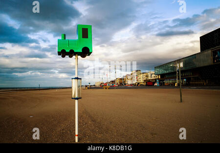 model toy train on pole in sand on Malo Les Bains beach Dunkirk France - Stock Photo