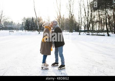 Senior couple in sunny winter nature ice skating. - Stock Photo