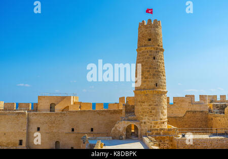 The tallest tower of Ribat with Tunisian flag on the top, the huge ramparts are seen on background, Monastir, Tunisia. - Stock Photo