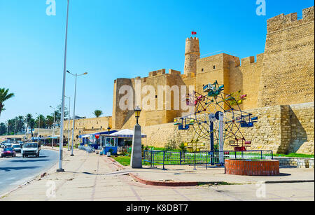 The small ferris wheel, outdoor cafes and bars at the walls of medieval Ribat fortress, located on the coast of - Stock Photo