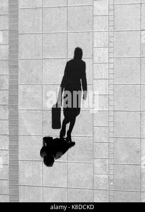 One woman , walking and holding a bag , shadow on the clean city sidewalk from above in black and white - Stock Photo