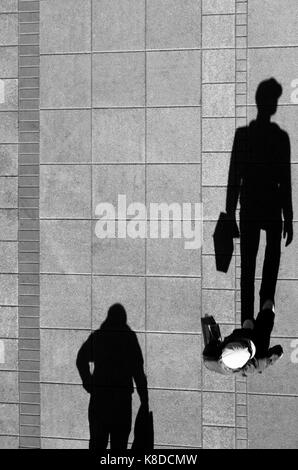 Two men , walking and holding bags , shadow on the clean city sidewalk from above in black and white - Stock Photo