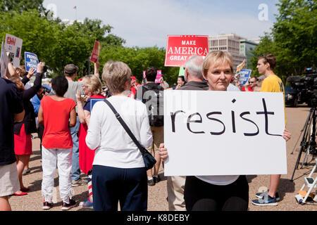 Anti-Trump protester holding 'Resist' sign at a pro-Trump rally - Washington, DC USA - Stock Photo