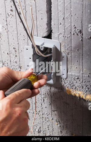 An electrician securing an electrical utility box using a screwdriver into insulated concrete form in Ontario, Canada. - Stock Photo