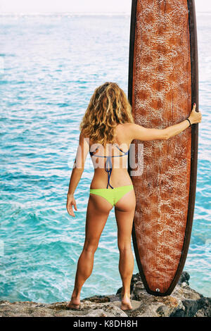 Beautiful surfer girl in bikini holding surf board stand on beach high cliff and look at ocean. Back view. People in water sport adventure camp.