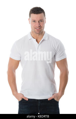 Portrait of smiling man in casuals standing with hands in pockets against white background - Stock Photo