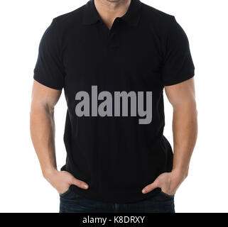 Midsection of man wearing blank black tshirt standing with hands in pockets against white background - Stock Photo