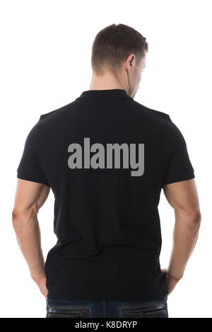 Rear view of man wearing blank black tshirt standing against white background - Stock Photo