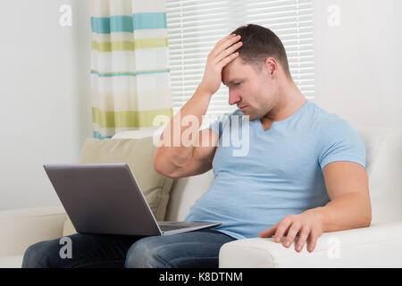 Upset mid adult man with laptop sitting on sofa at home - Stock Photo