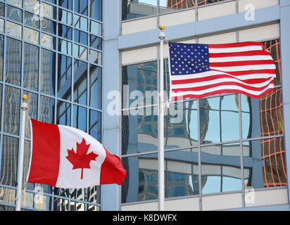 Waving flags of USA and Canada - Stock Photo