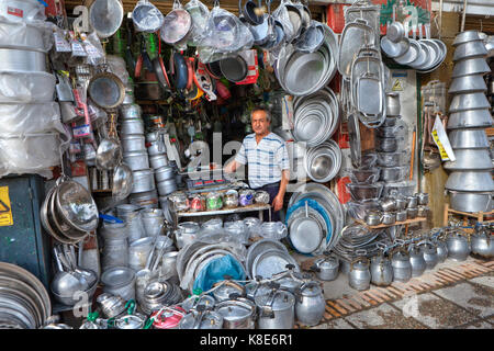 Fars Province, Shiraz, Iran - 18 april, 2017: Shop kitchen accessories made of metal, a trader surrounded by aluminum - Stock Photo