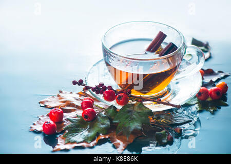 Glass tea cup in autumn still life with rain, leaves, berries on a wet background - Stock Photo