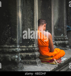Buddhist monk meditates in colonnade, temple complex of Angkor Wat, Angkor Archaeological Park, province of Siem - Stock Photo