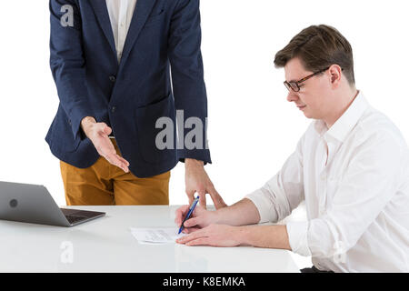 Two young businessmen signing contracts at office desk - Stock Photo