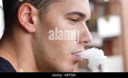 Man smoking ecig on balcony - Stock Photo